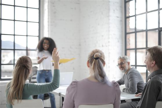 Canva - Female employee raising hand for asking question at conference in office boardroom.jpg
